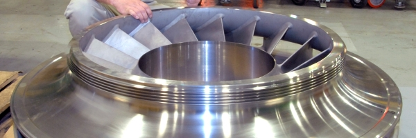 Ron Topper, supervisor of Rotor Division Machining and Assembly, looks over a large centrifugal compressor impeller. Many of the parts produced in the rotor department are as large as 80 inches in diameter